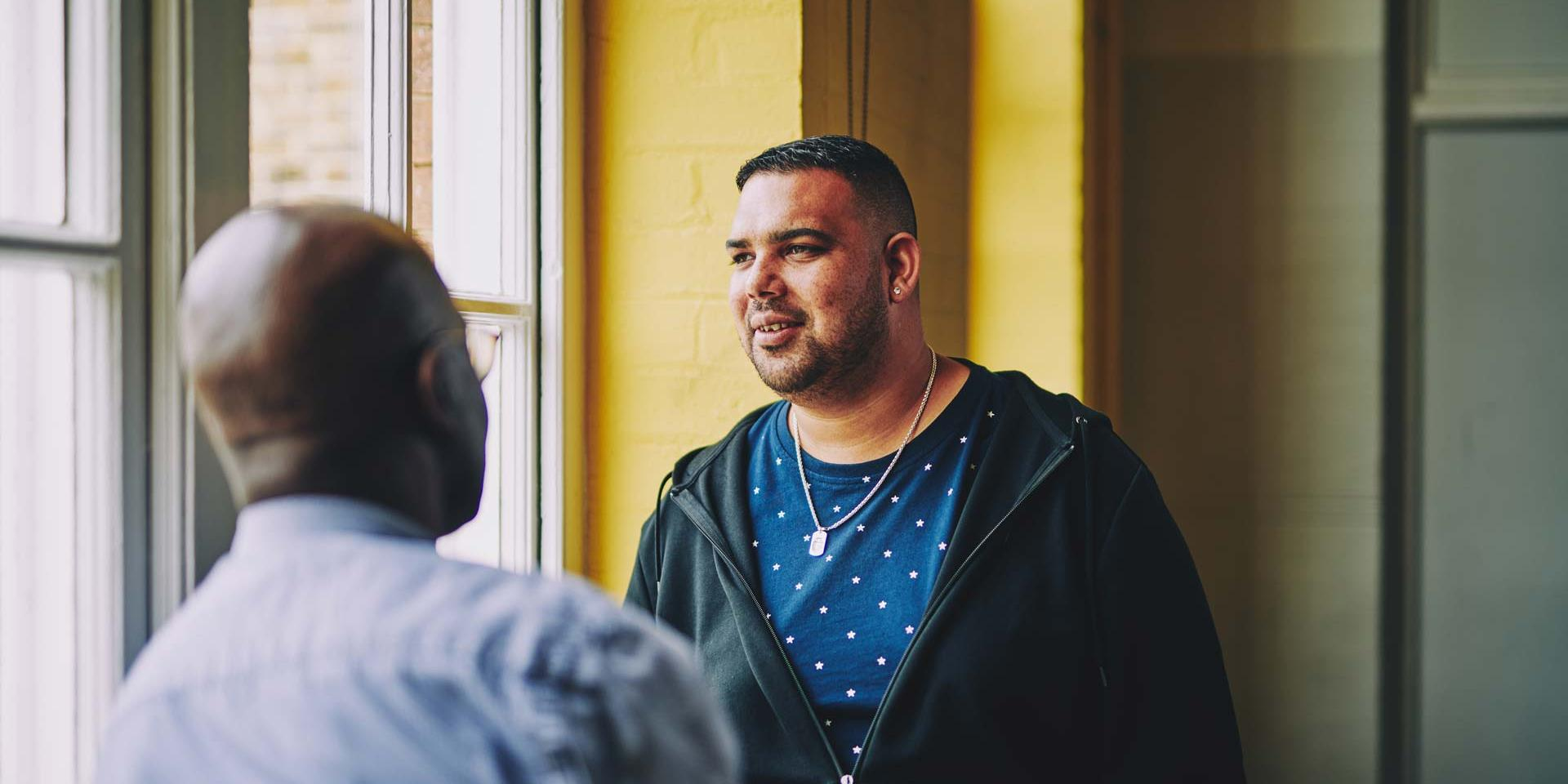 man having a conversation with another man and looking off into the distance