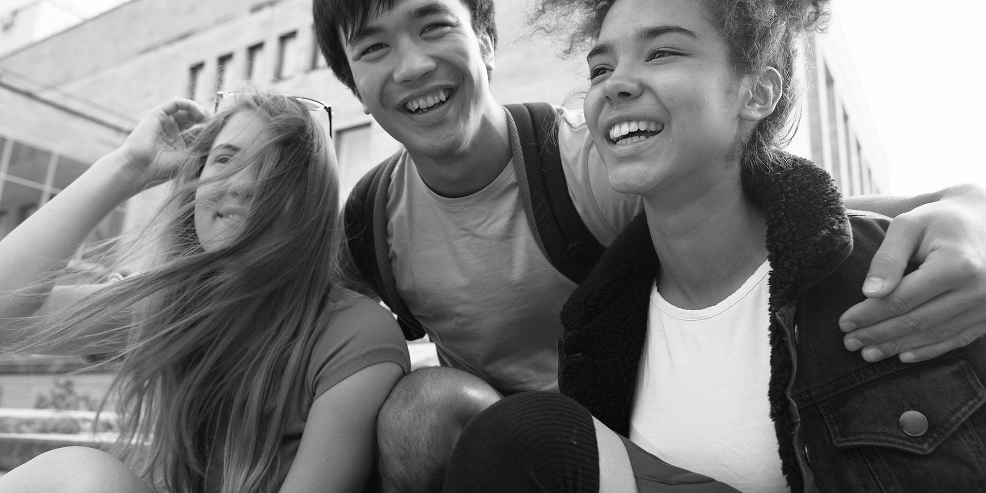 Three young people smiling and hugging