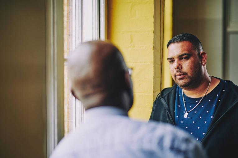 two men talking in a corridor