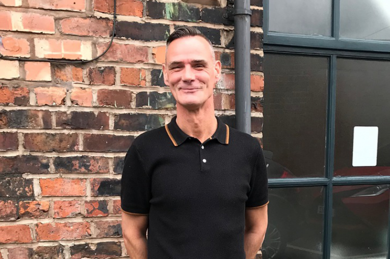 man in a black tshirt standing in front of a wall smiling