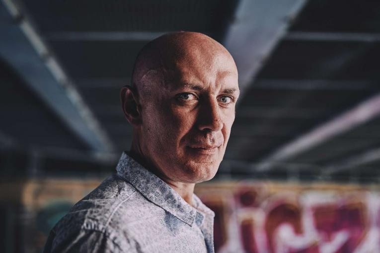 man with a straight face in front of some graffiti under a bridge