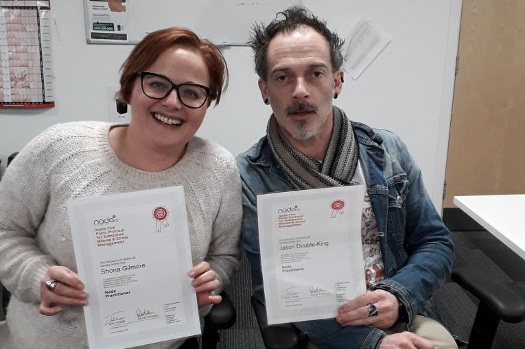 Two people in the Norfolk service with certificates for acupuncture