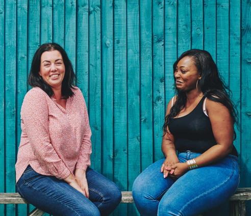 two women sitting on a bench talking and smiling