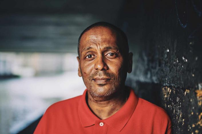 man standing under a bridge looking sincere with a straight face