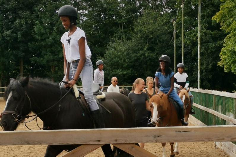 Young people riding horses