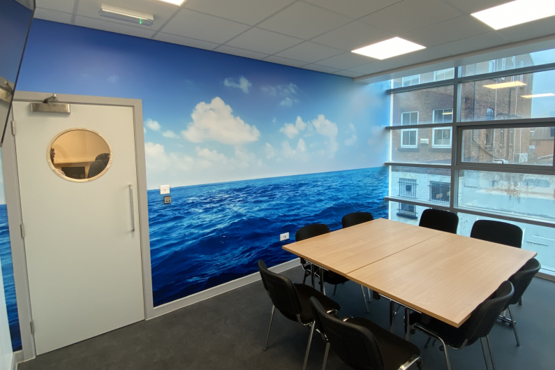 A meeting room at the Wirral hub with a table, chairs and a TV screen