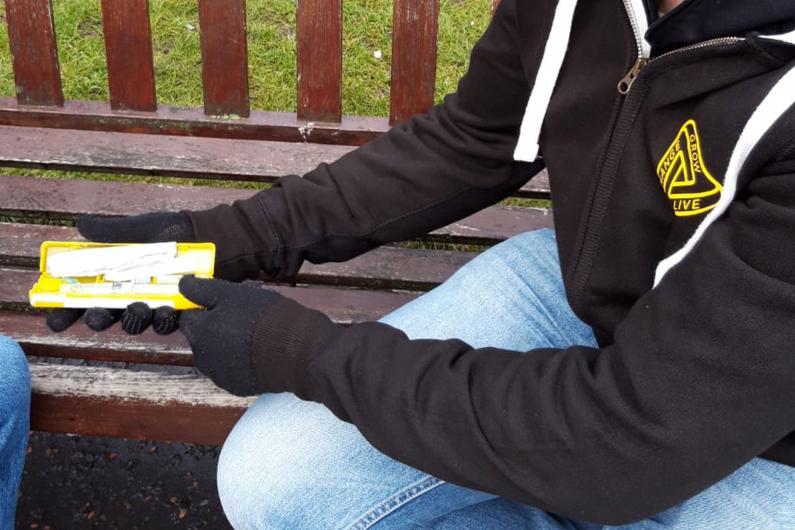 A man showing someone a naloxone kit